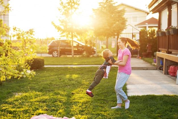 Het jonge meisje houdt haar leuke peuterbroer en spint hem op een mooie zonnige dag.