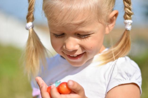 Het jonge meisje houdt smakelijke rode bessen in haar hand en lacht speel een de zomerdag