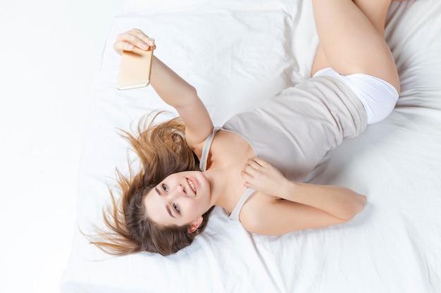 Het jonge meisje in bed met telefoon