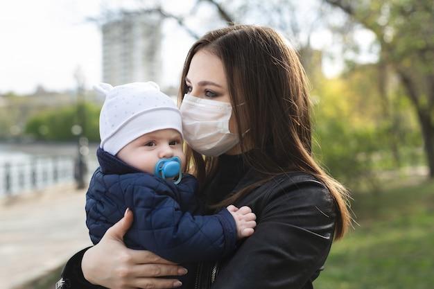 Het jonge meisje in een beschermend masker kust haar klein kind. covid-19