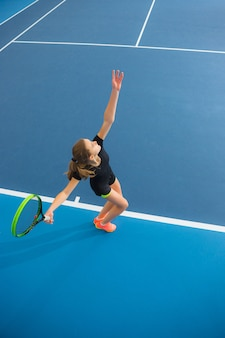 Het jonge meisje in een gesloten tennisbaan met bal