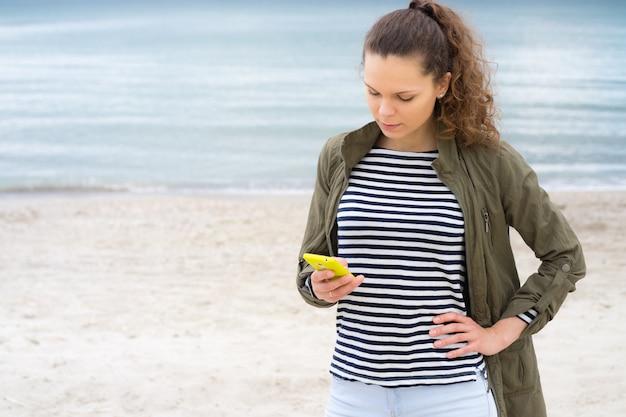 Het jonge meisje in een groen jasje gebruikt gele mobiele telefoon op het strand