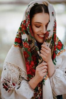 Het jonge meisje in een traditionele etnische jurk met een geborduurde cape op haar hoofd glimlacht