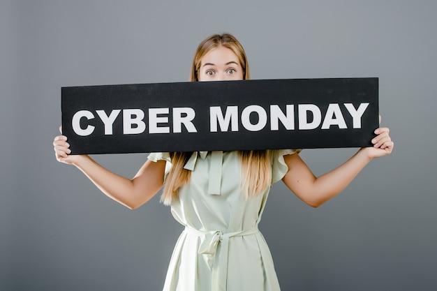 Het jonge meisje in kleding behandelt haar mond met het teken van de cybermaandag dat over grijs wordt geïsoleerd