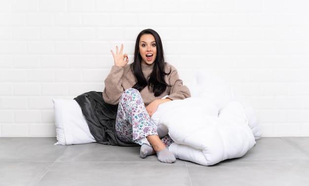 Het jonge meisje in pijamas bij binnen verraste en tonend ok teken