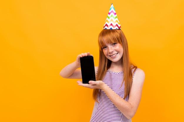 Het jonge meisje in purpet-shirt met rood haar glimlacht en houdt een telefoon die op geel wordt geïsoleerd