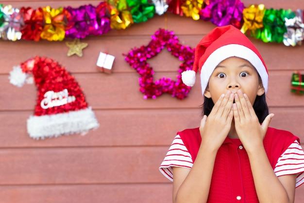 Het jonge meisje in rode kleding toont een verrassingsgezicht na het ontvangen van een grote gift in kerstmis.