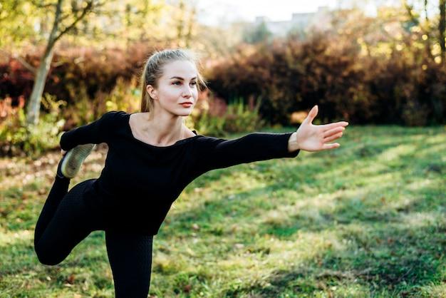 Het jonge meisje in zwarte sportkleding in het in evenwicht brengen stelt in openlucht.