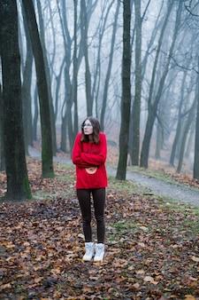 Het jonge meisje is alleen verloren in het mistige bos en voelt angst, depressie en eenzaamheid