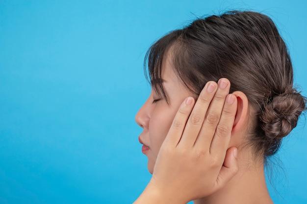 Het jonge meisje is ongelukkig en probeert de oren met haar handen op blauwe muur te sluiten.