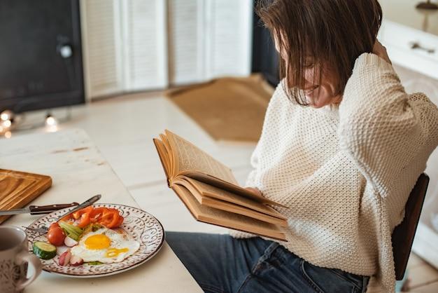 Het jonge meisje leest een oud boek bij het ontbijt. close-up handen en eettafel instelling. landelijke stijl. roerei en verse groenten en 's ochtends een interessant boek lezen?