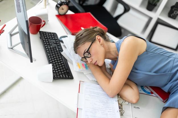 Het jonge meisje ligt met gesloten ogen op documenten op bureau in bureau.