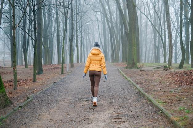 Het jonge meisje loopt 's ochtends alleen in het mistige park en voelt inspiratie