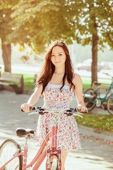 Het jonge meisje met de fiets in het park