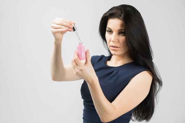 Het jonge meisje met een fles gezichtsserumzorg isoleerde wit