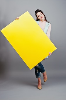 Het jonge meisje met gezicht houdt geel leeg document. jonge vrouw toont lege kaart. meisje met lang haarportret dat op grijze achtergrond wordt geïsoleerd.