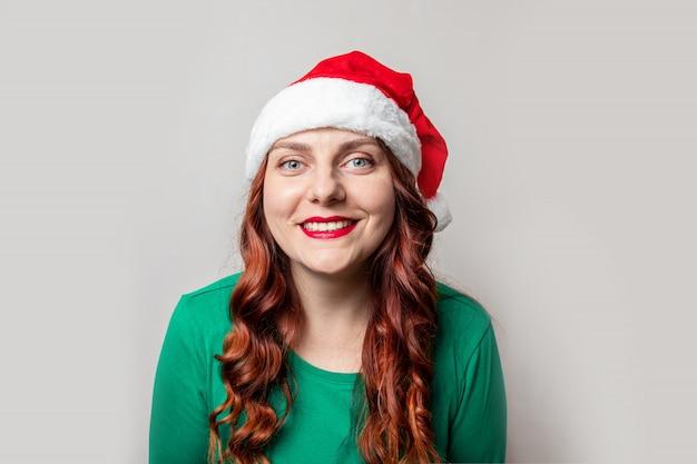 Het jonge meisje met rood krullend haar dat een rode santahoed draagt bekijkt de camera en glimlacht op een grijze achtergrond