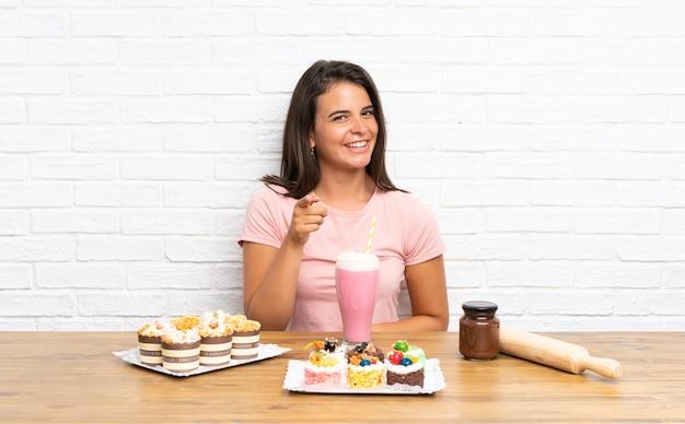 Het jonge meisje met veel verschillende minicakes richt vinger op u