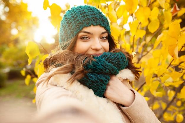 Het jonge meisje neemt een selfie op de mooie bladeren van de backgroungherfst.