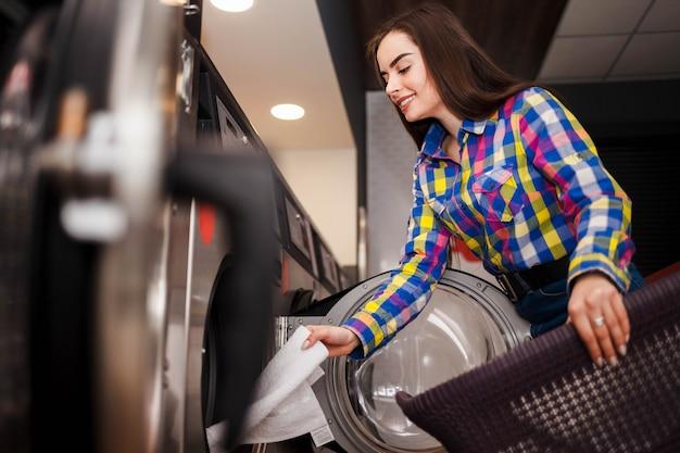 Het jonge meisje neemt gewassen kleren uit een wasmachine