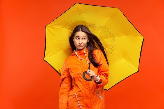 Het jonge meisje poseren in de studio in herfst jas geïsoleerd op rood. menselijke negatieve emoties. concept van het koude weer. vrouwelijke mode-concepten