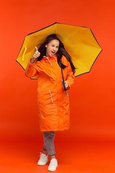 Het jonge meisje poseren in herfst jas geïsoleerd op rood