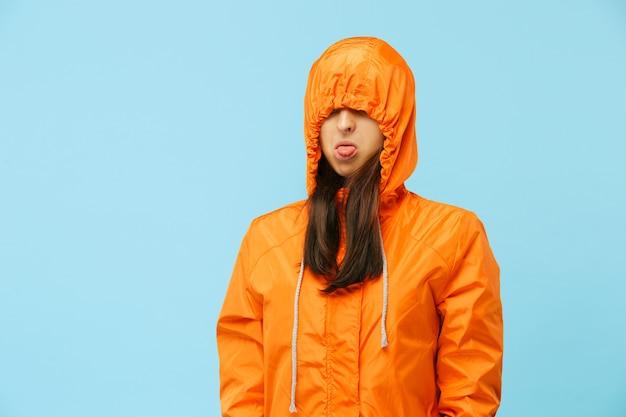 Het jonge meisje poseren in studio in herfst jas geïsoleerd op blauw.