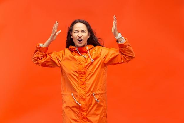 Het jonge meisje poseren in studio in herfst jas geïsoleerd op rood. menselijke negatieve emoties.