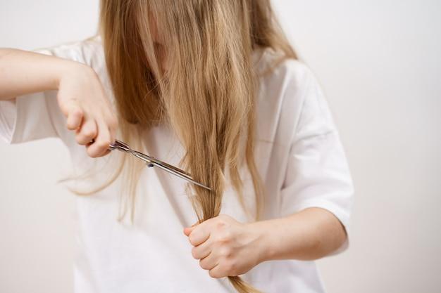 Het jonge meisje scheert haar lange haar met een schaar op een witte achtergrond. modieus kapsel voor de baby. kapper. grappen van kinderen. kapsel