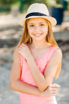 Het jonge meisje stellen met hand op borst op strand