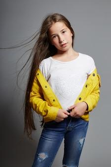 Het jonge meisje stellen op een grijze achtergrond, heldere vrolijke emoties op het gezicht van het meisje