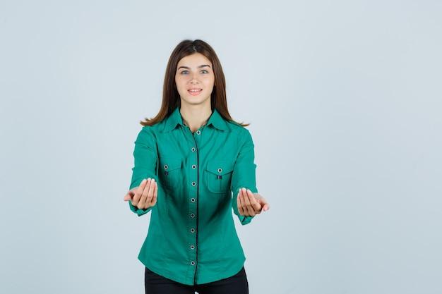 Het jonge meisje uitrekken zich tot een kom dient groene blouse, zwarte broek in en kijkt gelukkig, vooraanzicht.