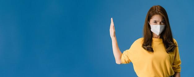 Het jonge meisje van azië draagt gezichtsmasker doet stop zingt met handpalm met negatieve uitdrukking en kijkt naar camera. sociale afstand nemen, quarantaine voor coronavirus. panoramische banner blauwe achtergrond.