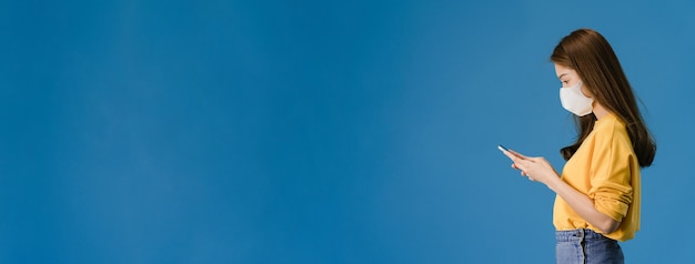 Het jonge meisje van azië draagt medisch gezichtsmasker gebruik mobiele telefoon met gekleed in casual doek. zelfisolatie, sociale afstand nemen, quarantaine voor coronavirus. panoramische banner blauwe achtergrond met kopie ruimte.