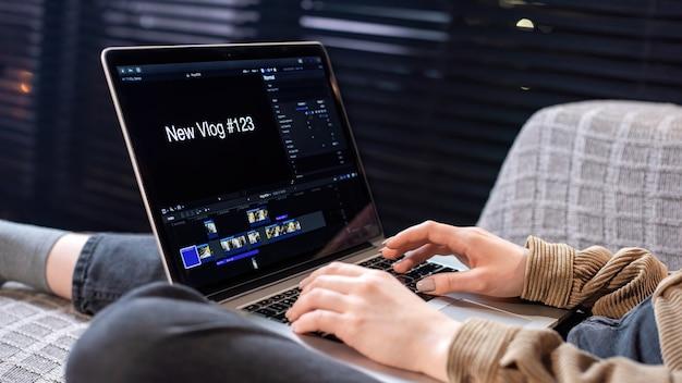 Het jonge meisje van de maker van de inhoud maakt op haar laptop een nieuwe vlog terwijl ze op de bank zit. werken met video vanuit huis