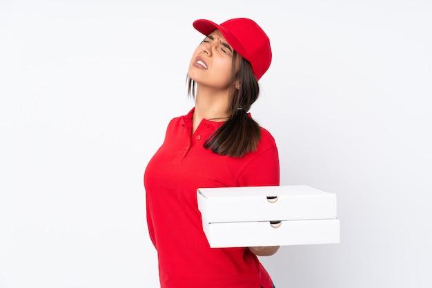 Het jonge meisje van de pizzakoerier over geïsoleerde witte muur die aan rugpijn lijdt voor het hebben van een inspanning