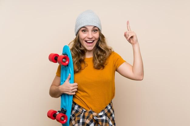 Het jonge meisje van de schaatserblonde over geïsoleerde muur die een groot idee benadrukken