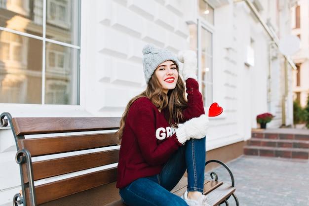 Het jonge meisje van gemiddelde lengte met lang haar in gebreide muts, jeans en witte handschoenen die op bank op straat zitten. ze houdt een karamelrood hart vast, glimlachend.