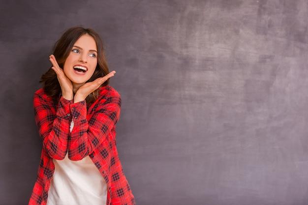 Het jonge meisje verheugt zich op een grijze achtergrond.