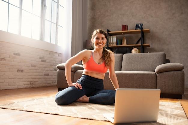 Het jonge meisje volgt met laptop oefent een gymnastiek uit. ze is thuis vanwege de quarantaine van coronavirus codiv-19