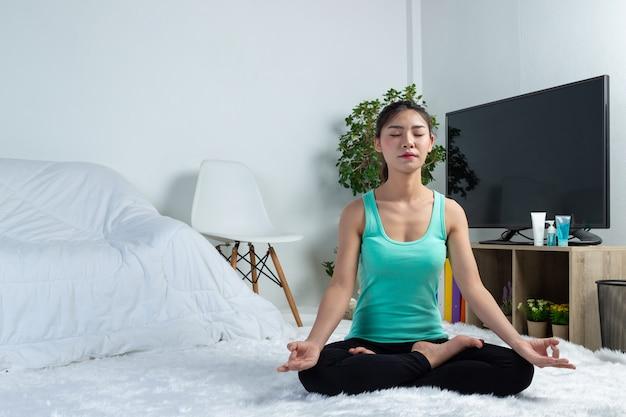 Het jonge meisje werkt thuis uit, zij oefent thuis yoga uit. concept gezond leven van virus.