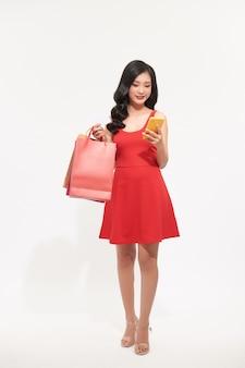 Het jonge meisje winkelt en gebruikt de telefoon die op witte achtergrond wordt geïsoleerd