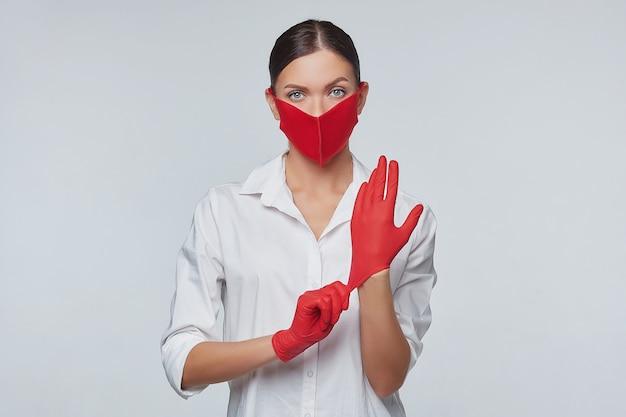 Het jonge meisje zet rode handschoenen en een gezichtsmasker aan.