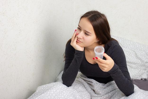 Het jonge meisje zit op een bed met een bank voor analyse