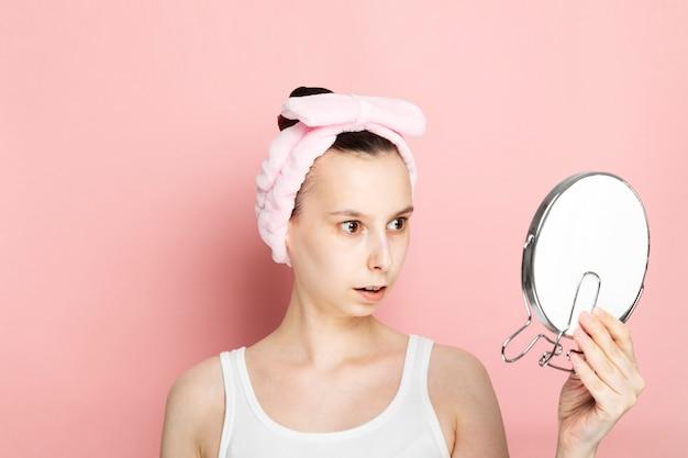 Het jonge meisje zonder make-up kijkt verrast in spiegel op roze ruimte