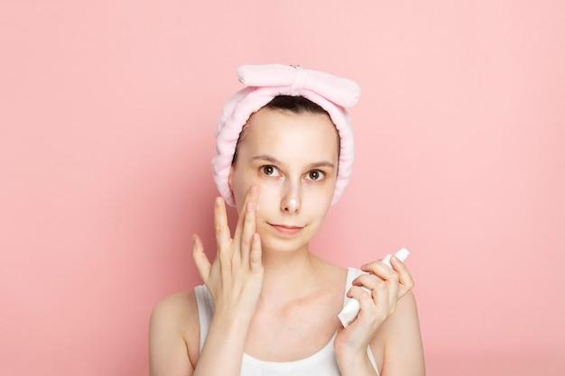 Het jonge meisje zonder make-up past gezichtslotion lotion op roze ruimte toe