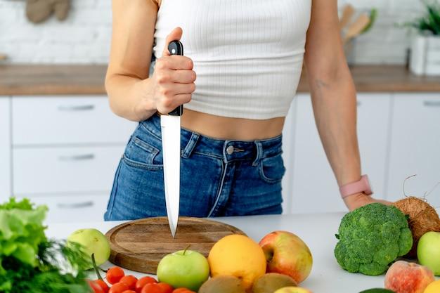 Het jonge mes van de vrouwenholding terwijl thuis het koken van verse groentesalade in keukenbinnenland