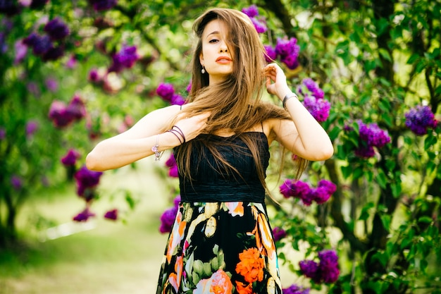Het jonge modieuze brunnettemeisje stellen voor camera in de lente bloeiend park.