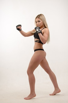 Het jonge mooie blonde sexy in dozen doende vrouw stellen met handschoenen op witte muur
