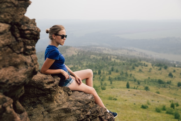 Het jonge mooie blonde toeristenmeisje zit op een rotsachtige richel van een rots en kijkt ver in de verte in de vroege mistige ochtend.
